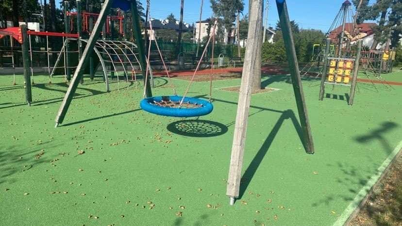 Na zdjęciu plac zabaw, z zieloną, bezpieczną nawierzchnią i widocznymi kilkoma zabawkami, na pierwszym planie huśtawka.
