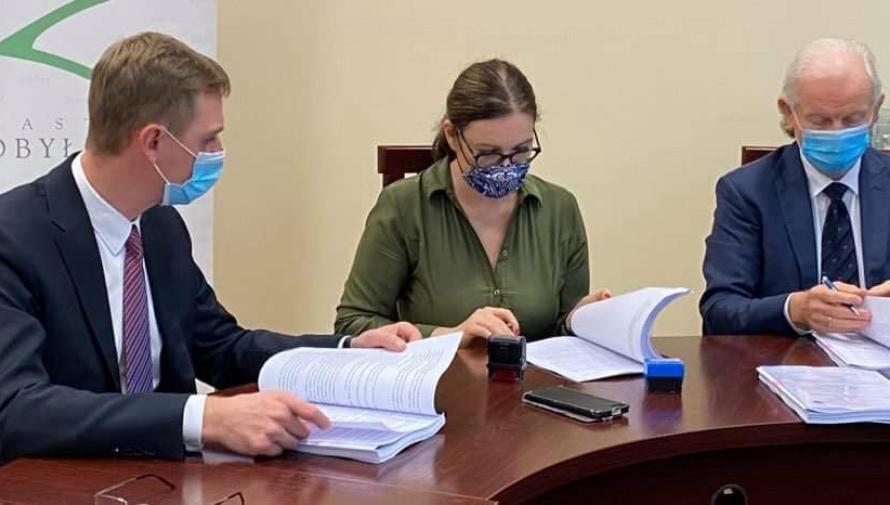 Na zdjęciu trzy osoby siedzące przy stole i podpisujące dokumenty. W środku burmistrz Edyta Zbieć w zielonej sukience, po jej lewej i prawej stronie dwóch  mężczyzn w ciemnych garniturach i krawatach.