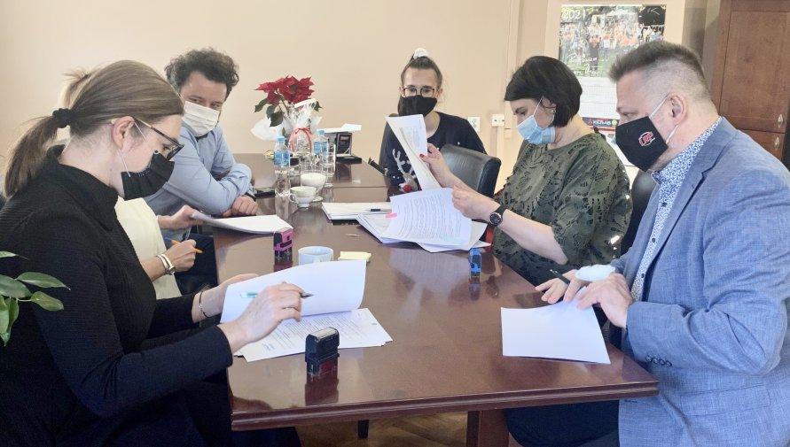 Na zdjęciu jest pięć osób siedzących przy stole, podpisujących lub czytających umowę.
