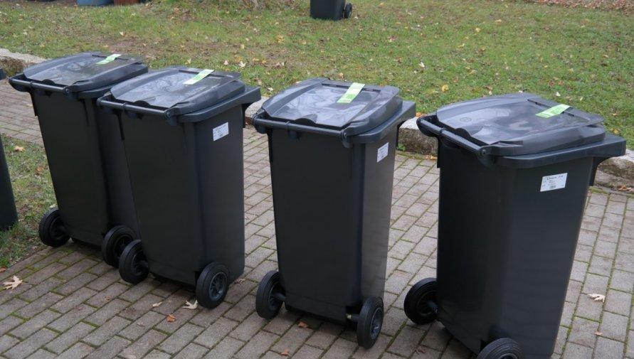 Cztery czarne zamykane kontery na śmieci stojące na chodniku