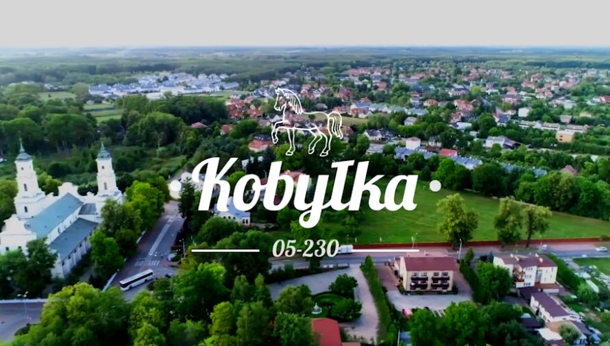 białe litery na kadrze z filmu przedstawiającym panoramę Kobyłki