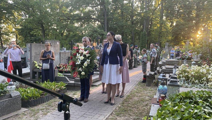 Burmistrz Edyta Zbieć i wiceburmistrz Grzegorz Owsianko stoją z kwiatami na cmentarzu, w tle harcerze