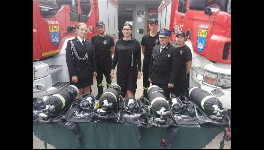 Burmistrz Kobyłki i Strażacy z OSP Kobyłka na tle samochodów strażackich