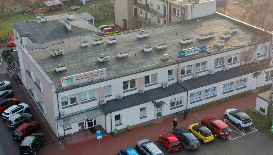 Widok z góry na budynek przychodni w Kobyłce, wokół widoczne parkujące samochody